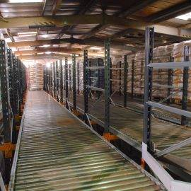 Image shows a warehouse with pallets on rollers as part of a pallet live system